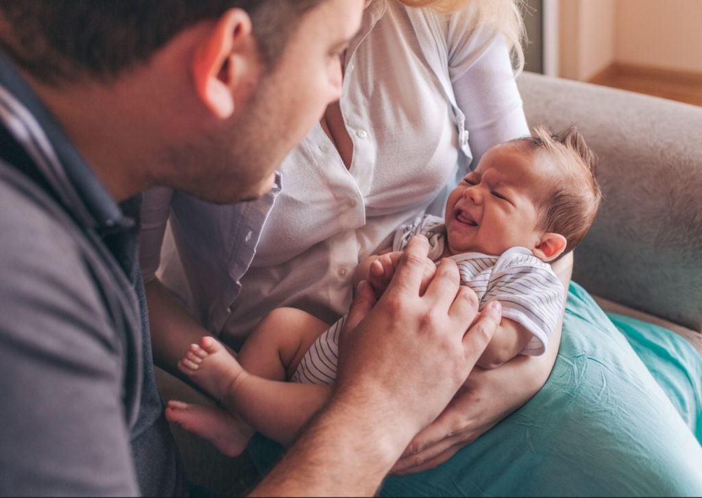 Cólico del lactante con fisioterapia, padres con bebé llorando